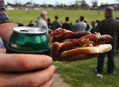 A fan is seen with a beer and barbequed sausages during the Northern Football League Grand Final match between Heidelberg and Greensborough at...