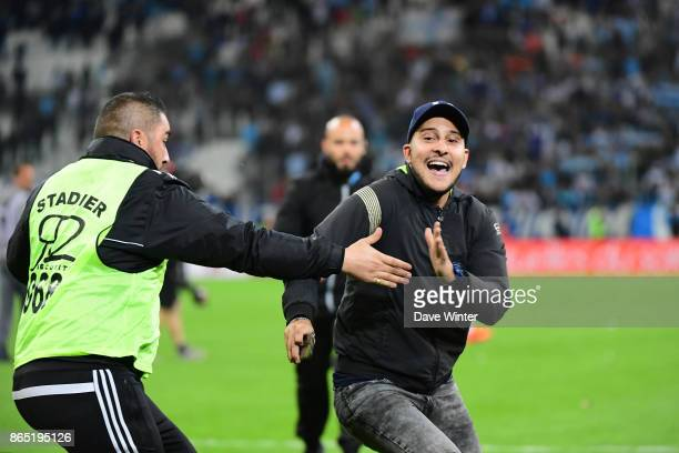 A fan is tackled by police and security after running on the pitch after the Ligue 1 match between Olympique Marseille and Paris Saint Germain at...