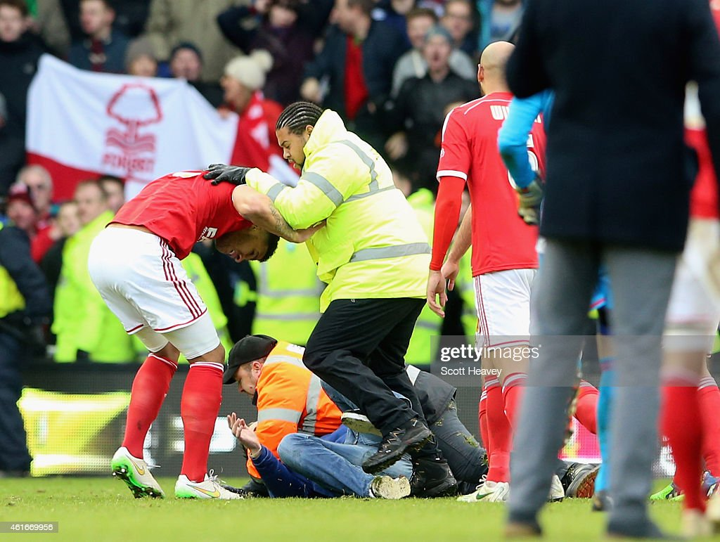 A fan is tackled by stewards after the final whistle during the Sky Bet Championship Match between Derby County and Nottingham Forest at iPro Stadium on January 17, 2015 in Derby, England.