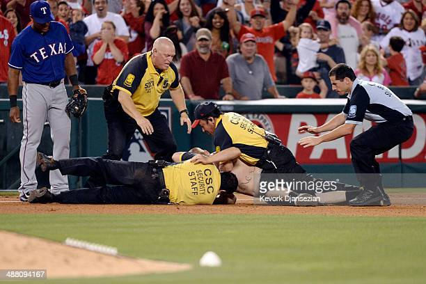 A fan is tackled to the ground by stadium security after entering the baseball field in the seventh inning while Adrian Beltre of theTexas Rangers...