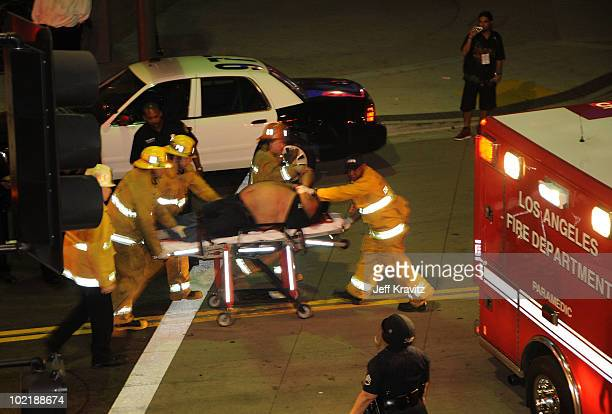A fan is taken by stretcher to an ambulance after clashing with the Los Angeles Police at the conclusion of the NBA Championship in front of the...