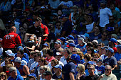 A fan is tended to by medical personnel after being struck with a foul ball during the game between the Chicago Cubs and the Atlanta Braves at...