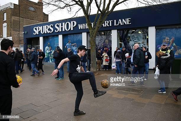 A fan kicks a ball outside a souvenir shop ahead of the English Premier League football match between Tottenham Hotspur and Arsenal at White Hart...