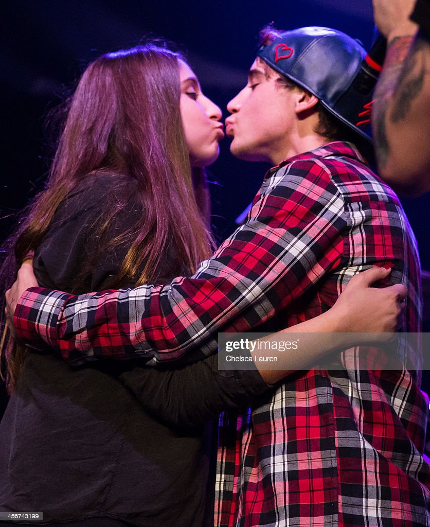 A fan kisses Youtube personality Luke Brooks of The Janoskians (R) on stage at DigiFest LA at Hollywood Palladium on December 14, 2013 in Hollywood, California.