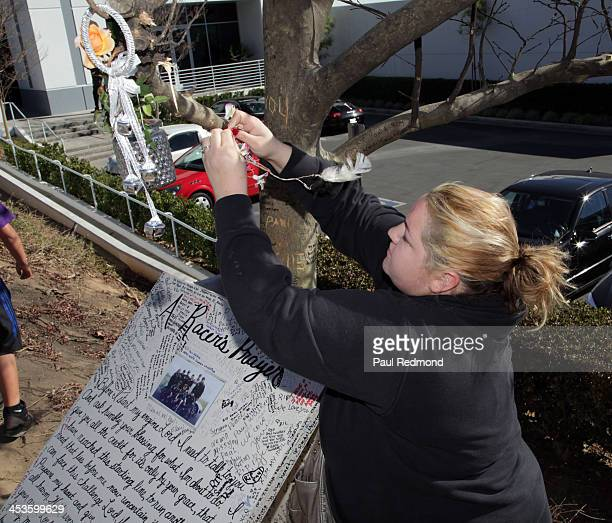 Fan Krystal Mora hangs a dream catcher on a tree at a memorial for Paul Walker at the site of his fatal car accident on December 4 2013 in Valencia...