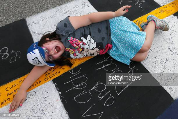 A fan lays on the startfinish line prior to the Monster Energy NASCAR Cup Series Pure Michigan 400 at Michigan International Speedway on August 13...