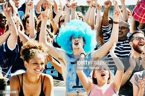 Fan leading crowd in cheer during football game : Stock Photo