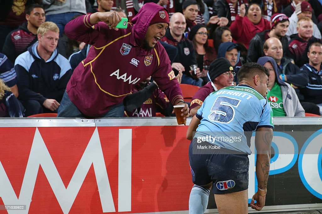 A fan leans over the fence to shout at Nathan Merritt of the Blues during game two of the ARL State of Origin series between the Queensland Maroons and the New South Wales Blues at Suncorp Stadium on June 26, 2013 in Brisbane, Australia.
