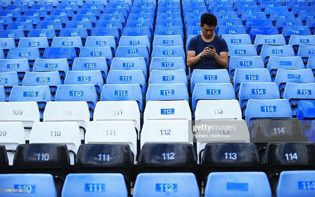 A fan looks at his mobile phone inside the ground prior to the Barclays Premier League match between Chelsea and Hull City at Stamford Bridge on August 18, 2013 in London, England.