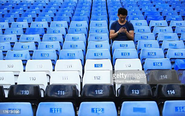 A fan looks at his mobile phone inside the ground prior to the Barclays Premier League match between Chelsea and Hull City at Stamford Bridge on...