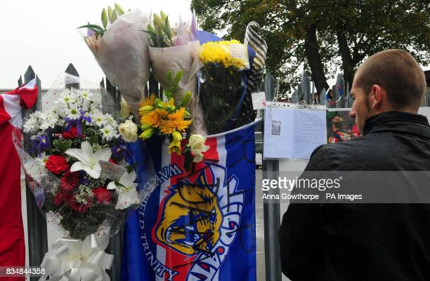 A fan looks at tributes that have been left on the gates of Belle Vue in Wakefield the home ground of Wakefield Trinity Wildcats in memory of player...