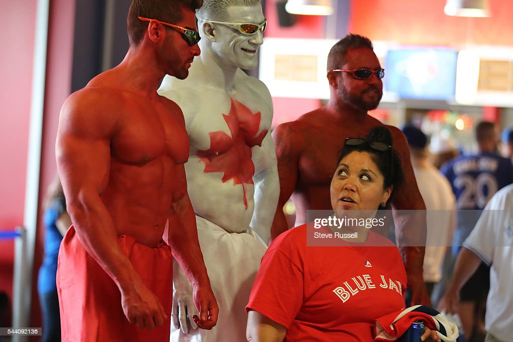 TORONTO, ON- JULY 1 - A fan looks back at some painted men as the Toronto Blue Jays play the Cleveland Indians on Canada Day at the Rogers Centre in Toronto. July 1, 2016.