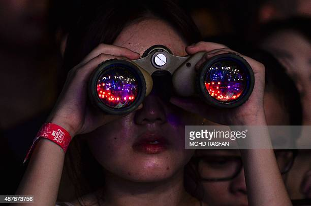 A fan looks through binoculars during the MTV World Stage Live in Malaysia 2015 concert at the Sunway Lagoon in Petaling Jaya outside Kuala Lumpur on...