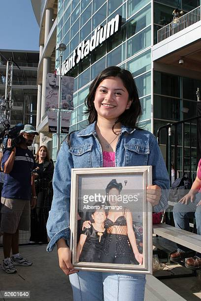 Fan Natali Sanchez poses with a photo of herself with Selena at the 'Selena Vive' concert at Reliant Stadium on April 7 2005 in Houston Texas
