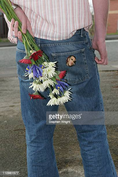 A fan of 1980s indie band The Smiths holding flowers and wearing a Morrissey badge on his jeans pocket Manchester UK 10th April 2005
