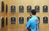 A fan of 2010 inductee Andre Dawson views the plaques of inducted members at the Baseball Hall of Fame and Museum during induction weekend on July 24...