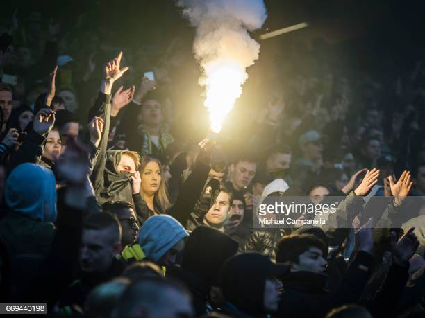 A fan of AIK lights a flare during an Allsvenskan match between AIK and Hammarby IF at Friends arena on April 17 2017 in Solna Sweden