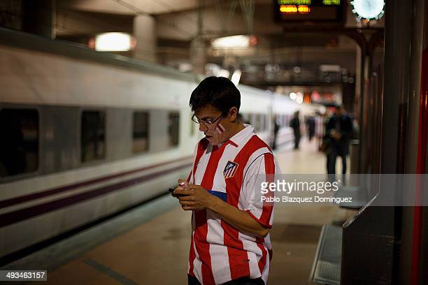 A fan of Atletico de Madrid checks his phone on the train's platform at Atocha Train Station before starting his trip to Lisbon a day before the UEFA...