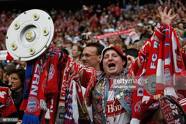 A fan of Bayern Muenchen holds up a replica of the German Championship trophy after the Bayern Munich 31 victory of the Bundesliga match between FC...