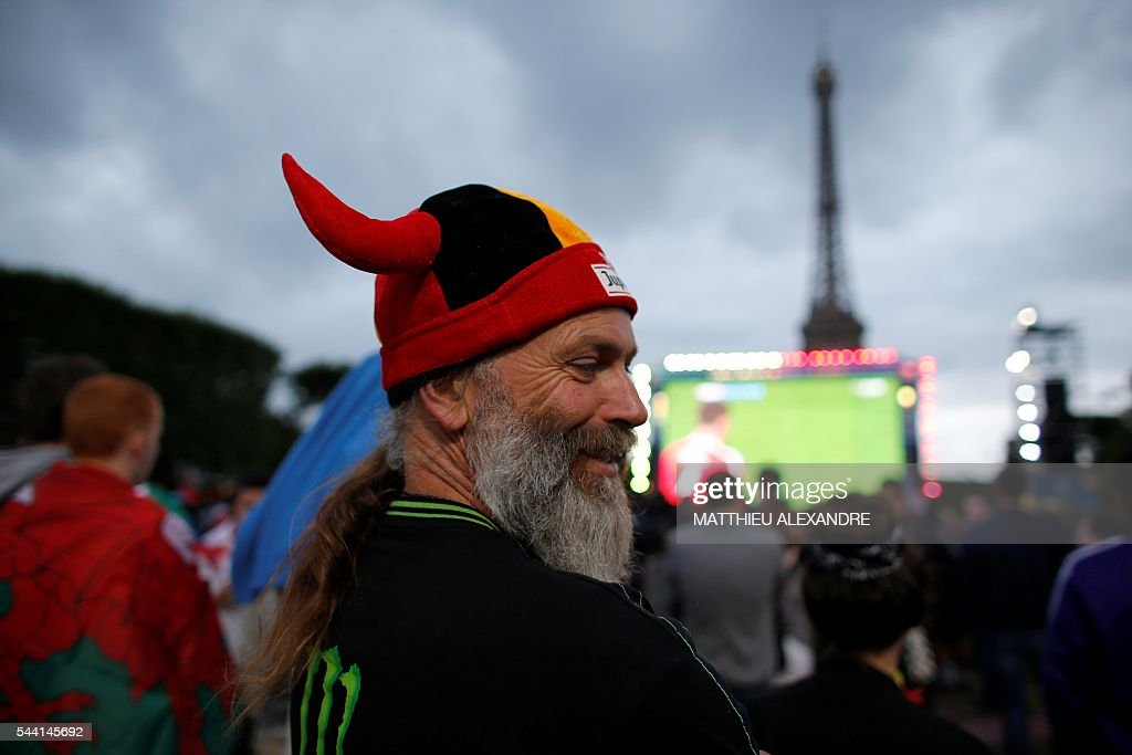 A fan of Belgium watches the Euro 2016 quarter-final football match between Wales and Belgium on a giant screen at the fan zone near the Eiffel Tower in Paris on July 1, 2016. / AFP / MATTHIEU