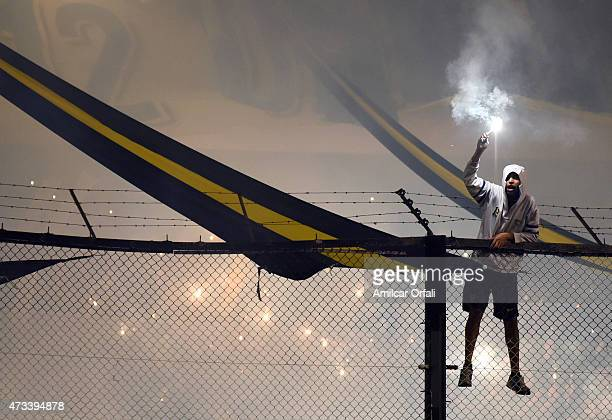 A fan of Boca Juniors holds a flare during a second leg match between Boca Juniors and River Plate as part of round of sixteen of Copa Bridgestone...