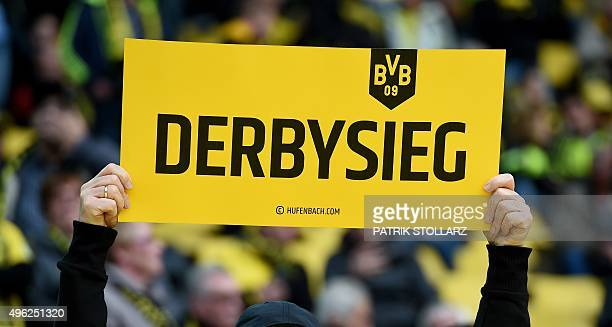 A fan of Borussia Dortmund holds a placard written 'Derby victory' prior to the German first division football Bundesliga match Borussia Dortmund vs...