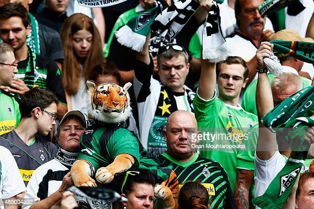 A fan of Borussia Monchengladbach holds a stuffed or toy tiger prior to the Bundesliga match between Borussia Moenchengladbach and 1 FSV Mainz 05...