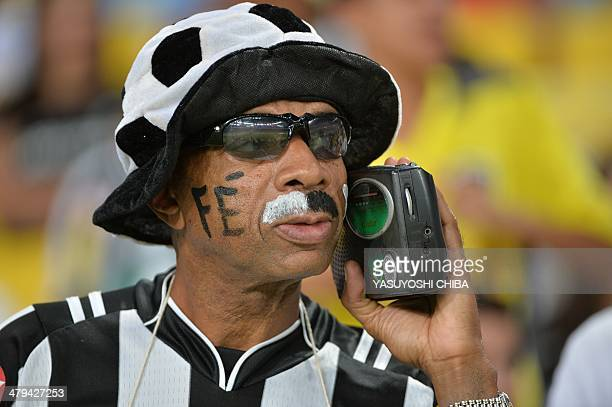 A fan of Brazil's Botafogo listens to his radio before the 2014 Copa Libertadores football match against Ecuador's Independiente del Valle at Mario...