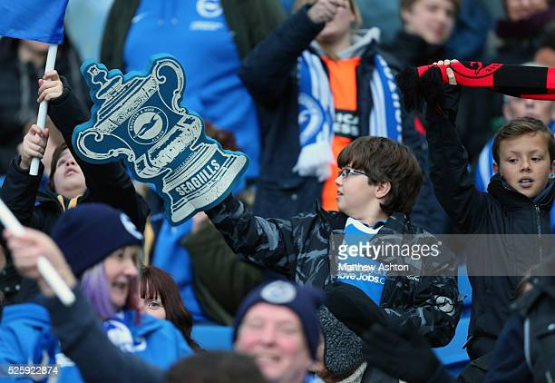 A fan of Brighton Hove Albion with a foam FA Cup Trophy