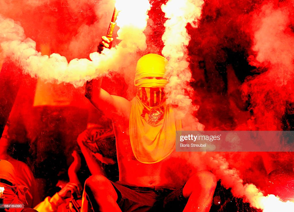 A fan of Brondby IF burns flares during to the UEFA Europa League third qualifying round first leg match between Hertha BSC Berlin and Brondby IF at...