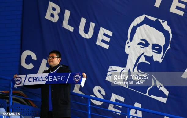 A fan of Chelsea has stands next to a banner of John Terry during the Premier League match between Chelsea and Southampton at Stamford Bridge on...
