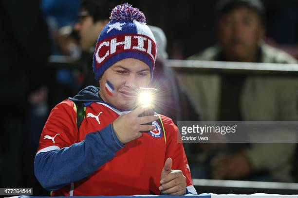 A fan of Chile takes a picture with her cellphone prior the 2015 Copa America Chile Group A match between Chile and Mexico at Nacional Stadium on...