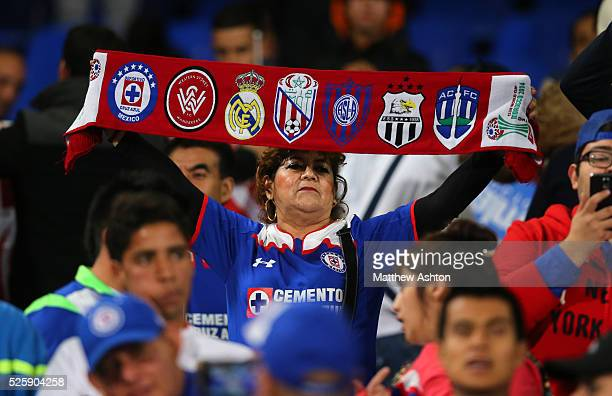 A fan of Cruz Azul holds up a scarf with the badges of all the teams taking part in the FIFA Club World Cup 2014 tournament