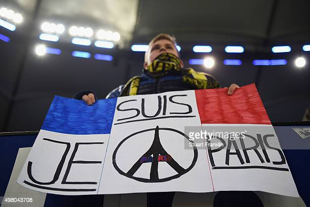 A fan of Dortmund holds a plackard of support for the 129 victims of the terrorist attack in Paris prior to the start of the Bundesliga match between...