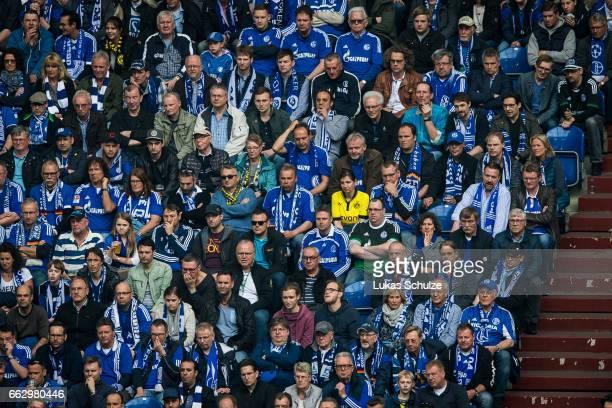 A fan of Dortmund sits between a lot of fans of Schalke during the Bundesliga match between FC Schalke 04 and Borussia Dortmund at VeltinsArena on...