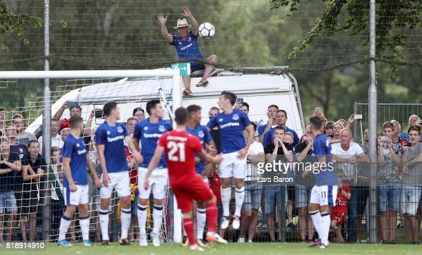 A fan of Everton sits on a car and tries to catch a free kick of Danny Holla of Twente during a preseason friendly match between FC Twente and...