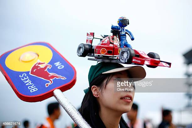 A fan of Fernando Alonso of Spain and Ferrari and former driver Mark Webber of Infiniti Red Bull Racing attends Qualifying for the Japanese Formula...