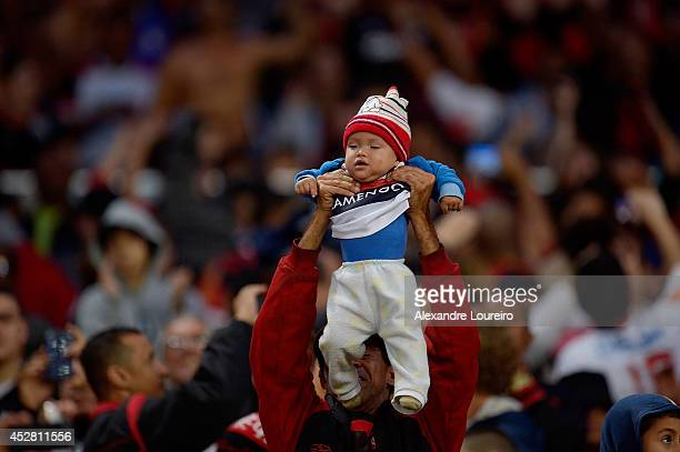 A fan of Flamengo holds his son during the match between Flamengo and Botafogo as part of Brasileirao Series A 2014 on July 27 2014 in Rio de Janeiro...