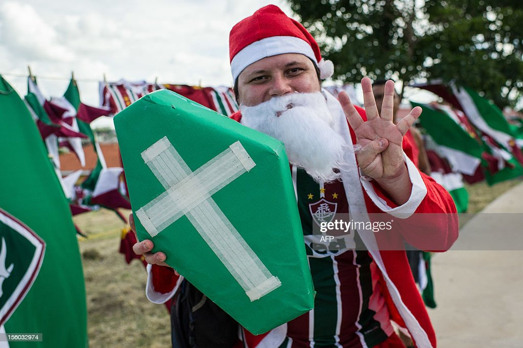 A fan of Fluminense fancy dressed as Santa Claus holds a coffin representing their rival club Palmeiras before their Brazilian championship football match at Prudentao stadium in Presidente Prudente, Sao Paulo state, Brazil on Novemeber 11, 2012. AFP PHOTO/Yasuyoshi CHIBA
