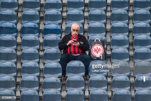 A fan of Frankfurt looks on his smartphone prior to the Bundesliga match between Eintracht Frankfurt and VfL Wolfsburg at CommerzbankArena on May 6...