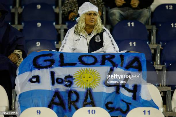 A fan of Gimnasia y Esgrima display a flag in memory of the 44 crew members of Argentine missing submarine 'ARA San Juan' prior a match between...