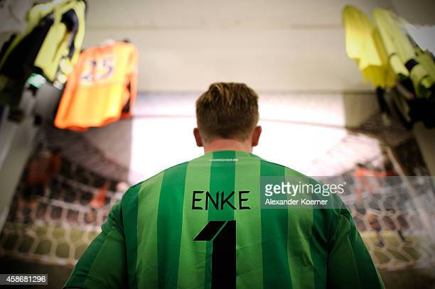 A fan of goalkeeper Robert Enke wearing a soccer jersey of Enke stands in front of a large billboard at the special exhibition 'ROBERT gedENKEn' at...