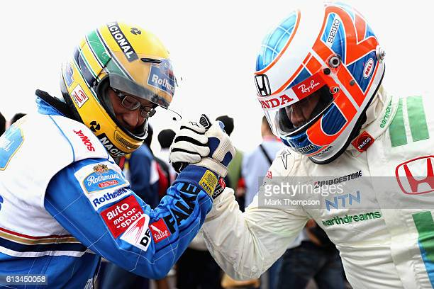 A fan of Jenson Button of Great Britain and McLaren Honda has an arm wrestle with a fan of Ayrton Senna in the fan zone before the Formula One Grand...