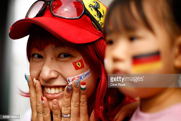 A fan of Kimi Raikkonen of Finland and Ferrari poses for the camera during Qualifying for the Japanese Formula One Grand Prix at Suzuka Circuit on...