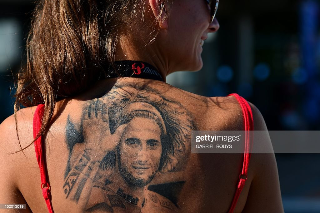 A fan of late Italian rider Marco Simoncelli shows her tatoo during the qualifying practice of the San Marino Moto Grand Prix on September 15, 2012 at the Misano world circuit in Missano Adriatico. Simoncelli died after an accident during the 2011 Malaysian Grand Prix at Sepang on 23 October 2011.