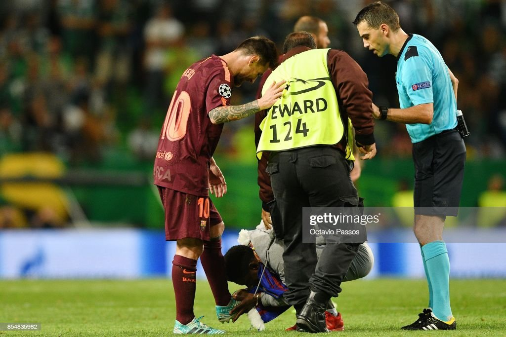 A fan of Lionel Messi of FC Barcelona invades the pitch and kiss the boots of Messi during the UEFA Champions League group D match between Sporting CP and FC Barcelona at Estadio Jose Alvalade on September 27, 2017 in Lisbon, Portugal.