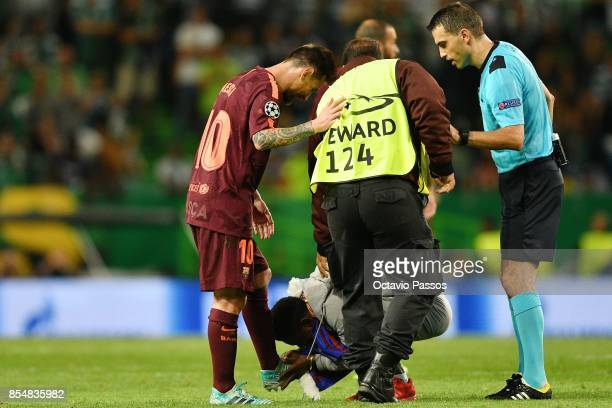 A fan of Lionel Messi of FC Barcelona invades the pitch and kiss the boots of Messi during the UEFA Champions League group D match between Sporting...