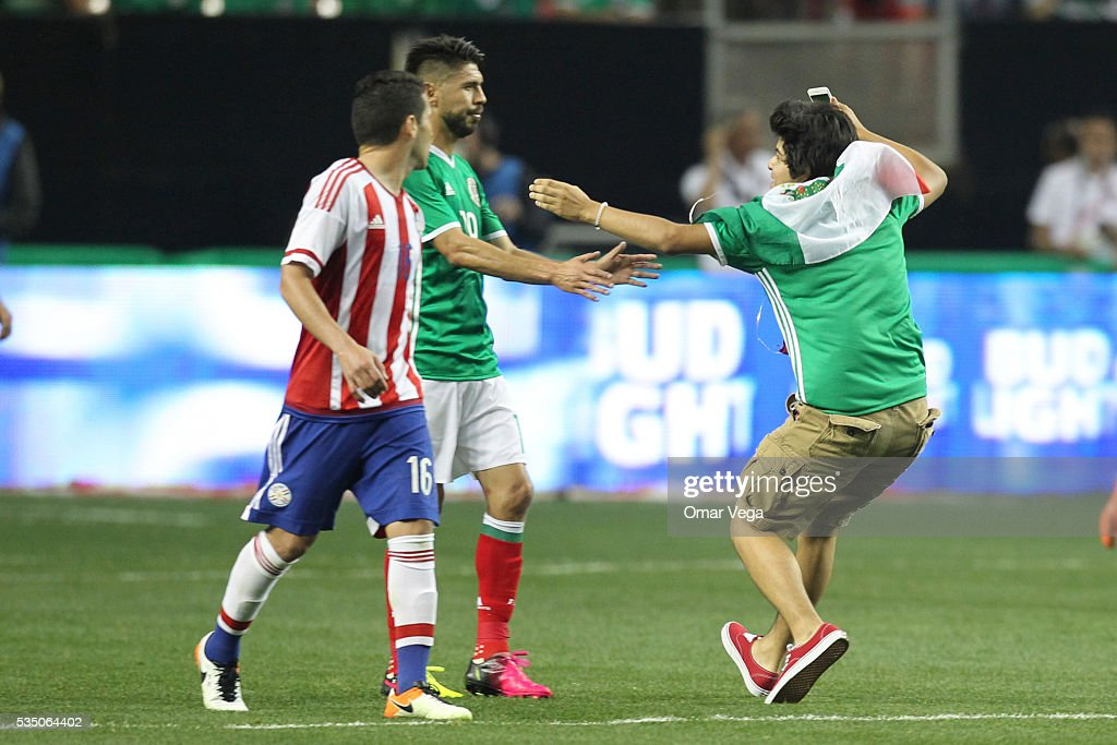 Fan of Mexico streaks onto the pitch during the International Friendly between Mexico and Paraguay at Georgia Dome on May 28, 2016 in Atlanta, Georgia.