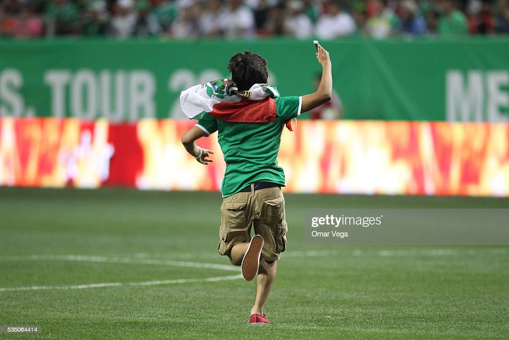 Fan of Mexico streaks onto the pitch during the International Friendly between Mexico and Paraguay at Georgia Dome on May 28 2016 in Atlanta Georgia