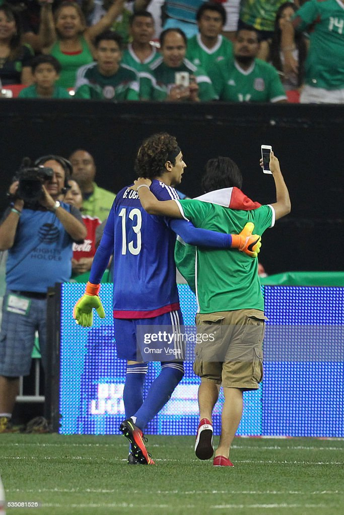 Fan of Mexico takes a selfie with Guillermo Ochoa goalkeeper of Mexico after entering onto the pitch during the International Friendly between Mexico...